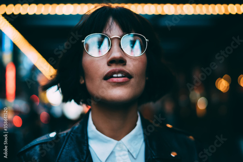 Obraz na płótnie Youthful female traveller in stylish spectacles for vision correction spending t