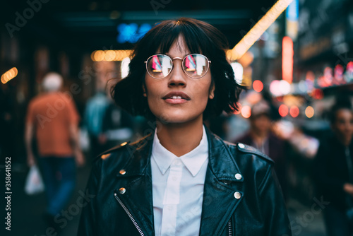 Carta da parati Trendy dressed tourist in stylish eyeglasses with neon reflection looking up dur