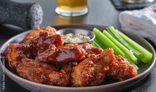 Leinwand Poster boneless chicken wings covered in honey garlic bbq sauce with ranch and celery