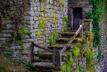 Beautiful Old Stairway Leading To The Door Of A Castle With Stone Walls Covered In Moss