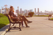 Couple Relaxing On City Bench.