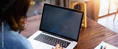 Fotografie, Obraz Mockup image of a woman using laptop with blank screen on wooden table