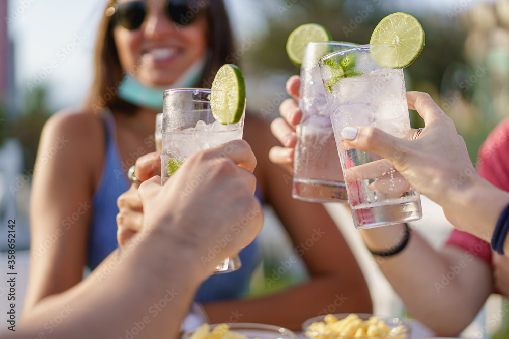 Fototapeta Friends drinking cocktails in an outdoors snack bar restaurant in the summer wearing face mask on to be protected from coronavirus - Happy people cheering with mojito and having fun