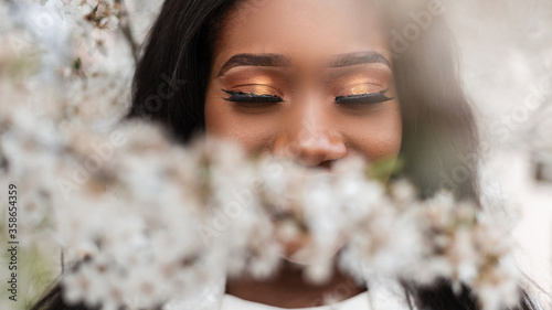 Fotografía Close-up face of a beautiful happy african black woman with closed eyes in flowers on a spring blooming day