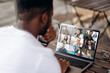 Leinwandbild Motiv Video call. Video conference. Successful African American freelancer communicate by a video conference with his colleagues using a laptop while sitting in cafe in a summer terrace
