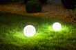illumination backyard light garden with 2 electric ground lanterns with round diffuser lamp in the green grass lawn in outdoor park with landscaping, dark closeup illuminate night scene nobody.