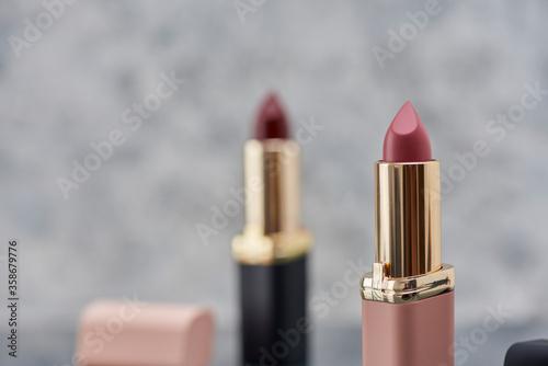 Fotografie, Obraz Lápiz labial Rojo con negro y rosa sobre una superficie de mármol con las tapas