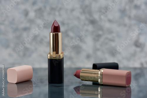 Fototapeta Lápiz labial Rojo con negro y rosa sobre una superficie de mármol con las tapas