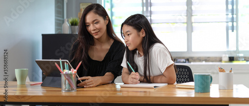 Valokuva Private tutor and student homeschooling with digital tablet and stationery on wo