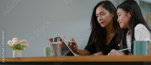 Mother and daughter homeschooling with digital tablet on wooden worktable in liv Fototapete