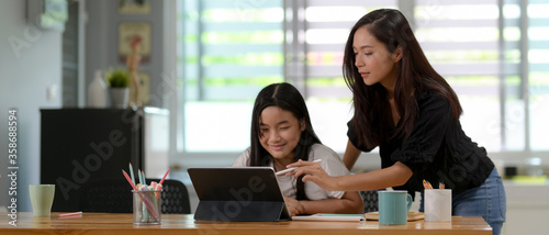 Close up view of mother and daughter homeschooling with digital tablet Canvas-taulu