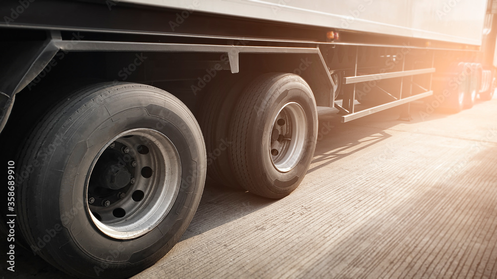 Fototapeta Closeup a truck wheels of semi truck trailer on parking. Road freight transportation.