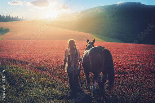 Young beautiful dreadded girl outdoors with her horse.