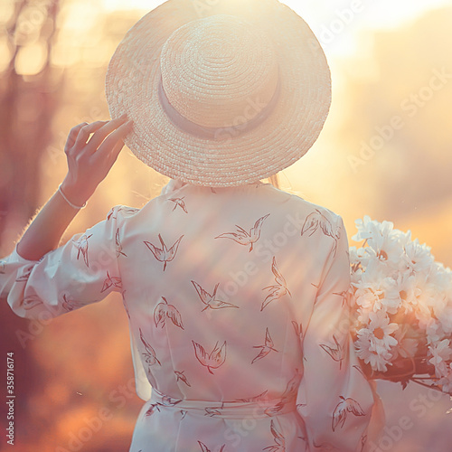 Stampa su Tela romantic girl in a straw hat view from the back / model girl poses in the summer