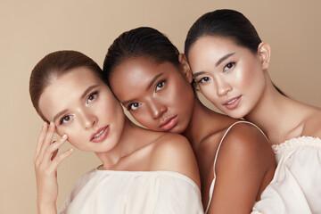 Ljepota. Skupina modela raznolikosti Portret. Multietničke žene s različitim tipovima kože poziraju na bež pozadini. Nježne multikulturne djevojke koje stoje zajedno i gledaju u kameru.