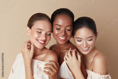 Obraz Beauty. Diverse Group Of Ethnic Women Portrait. Happy Different Ethnicity Models Standing Together With Closed Eyes And Smiling. Gorgeous Multi-Ethnic Girls With Nude Makeup Against Beige Background. - fototapety do salonu