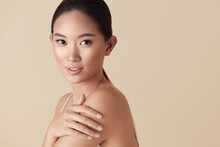 Woman. Asian Model Beauty Portrait. Beautiful Female Touches Her Shoulder And Looking At Camera. Tender Girl With Perfect Glowing Skin And Nude Natural Makeup Posing Against Beige Background.