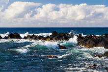 Waves Rolling Towards Shore  Near South Point, In Hawaii's Big Island. Volcanic Rocks In The Surf. Blue Pacific Ocean Stretches To The Horizon; Overhead Is A Cloud-filled Sky.