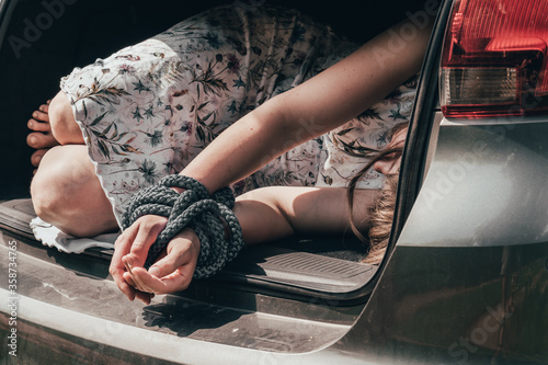 Canvas Print Woman with tied hands inside car trunk - kidnapping