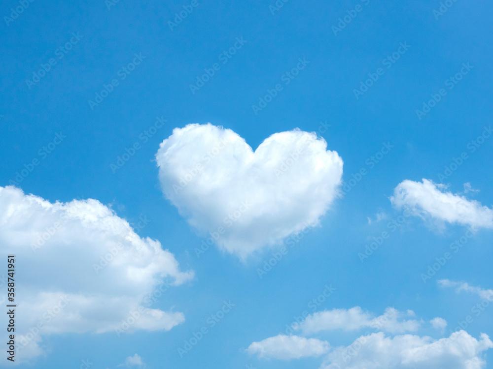 Fototapeta White heart shaped cloud in the blue sky background