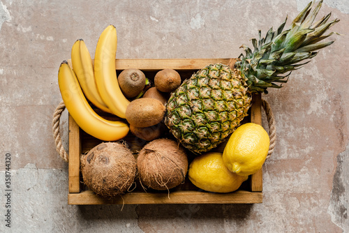 top view of ripe tropical fruits in wooden box on weathered surface