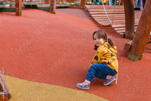 Obraz Child playing outdoors. A little girl climbs on the Playground. Modern and safe children's Playground. Wooden equipment for children's joint games. Fun and active childhood. - fototapety do salonu