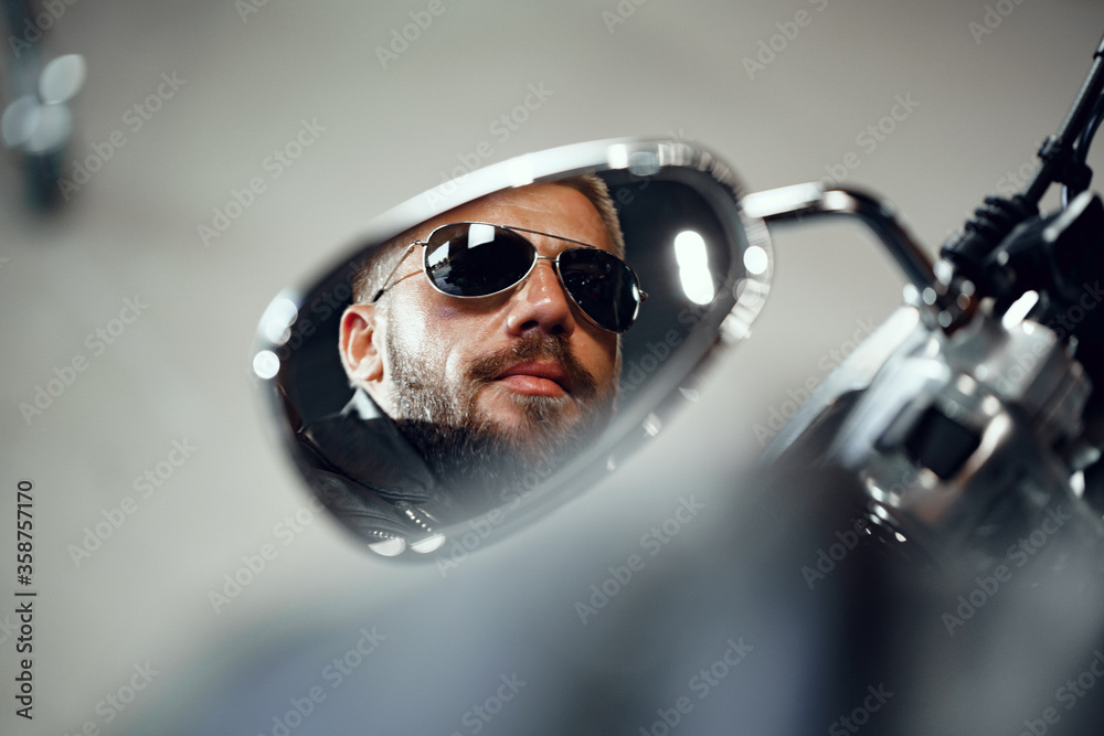 Fototapeta Reflection in the motorcycle mirror of a man driver in sunglasses