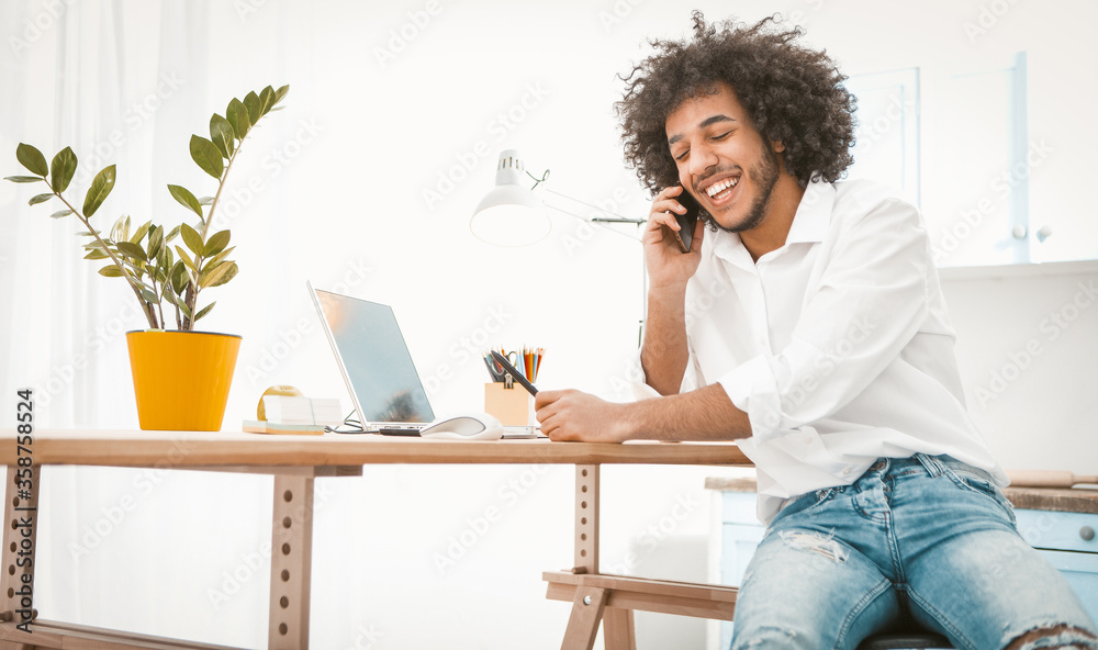 Fototapeta Side view of young entrepreneur or student talking mobile phone while working from home. Charming Arab guy chatting on smart phone with friends or customers. Tinted image.