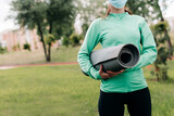 Cropped view of sportswoman in medical mask holding fitness mat in park