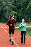 Couple in medical masks jogging together on running path in park