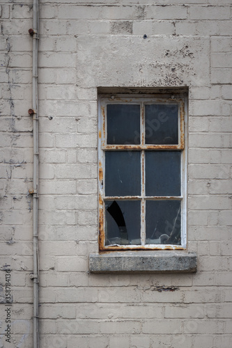 Photo Rusted, decaying six pane metal window with cracked, broken glass recessed into