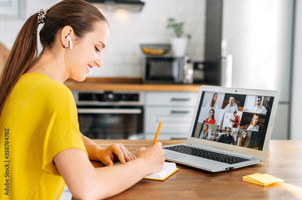 Fototapeta Side view of young woman watching on laptop display with a group of multiracial people on it and writing notes. Video call, online conference, webinar