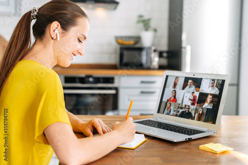 Side view of young woman watching on laptop display with a group of multiracial people on it and writing notes Canvas Print