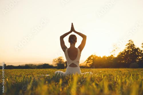 Young woman practicing yoga on nature. Fototapeta