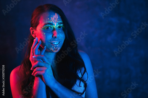 Portrait of calm young woman with UV body art Wallpaper Mural