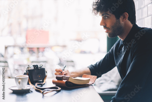 Photo Side view of male amateur dressed in trendy black shirt writing down text information in notepad sitting at coffee table with vintage camera in stylish cafeteria interior