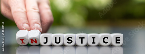 Hand turns dice and changes the word injustice to justice. Canvas Print