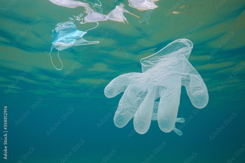 Fototapeta Glove and face mask underwater, ocean plastic waste pollution since coronavirus COVID-19 pandemic