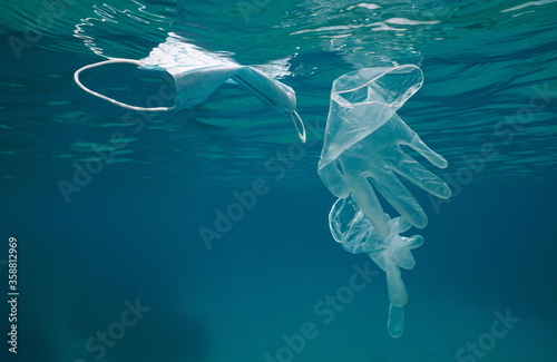 Gloves and face mask underwater in the sea, plastic waste pollution since coronavirus COVID-19 pandemic #358812969