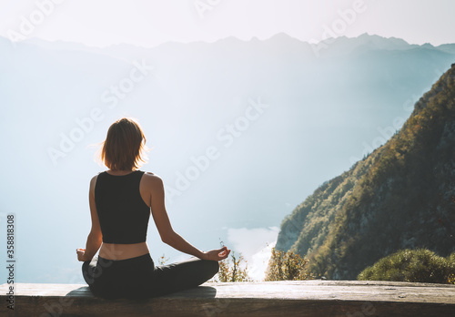 Foto Young woman is meditating in mountains.