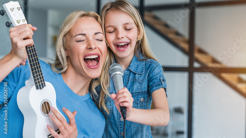 Fototapeta Caucasian mother with little girl singing in karaoke at home