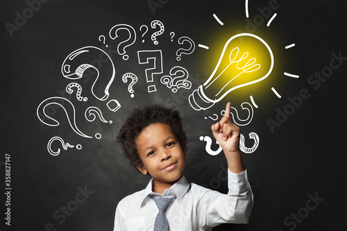 Obraz Successful black child student pointing at lightbulb. Brainstorming and idea concept - fototapety do salonu