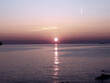 Genova, Italy - 06/18/2020: Beautiful photography of the sunset over the sea and clouds reflection on the water. Panoramic view to the ligurian coast in spring days.