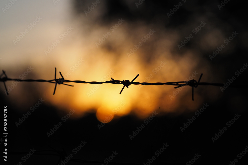 Fototapeta Sunset Behind The Barbed Wire..