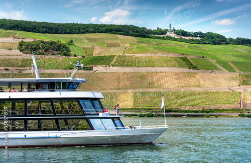 Rüdesheim am Rhein – Ausflugschiff mit Niederwalddenkmal Germania und Weinbergen, Blick von Bingen #358871959