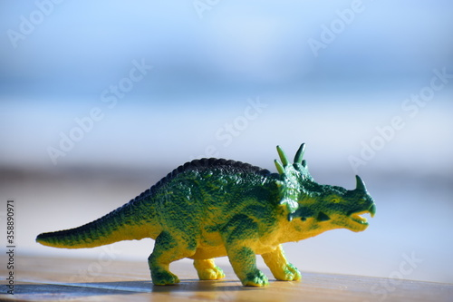 Obraz na plátně Dinosaur toy standing outside with the beach and ocean in the background