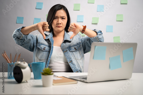 Asian woman working on a laptop annoy and showing thumb down at home office Canvas Print