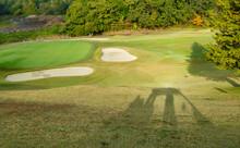 ゴルフの乗用カートの影が芝生の上に落ちているある日の午後の風景