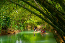 Falmouth, Jamaica. Tourists On Bamboo Raft Rides On Martha Brae River. Relaxing Scenic Tour Through Countryside Landscape Under Canopy Of Trees. People Enjoy Summer Vacation Activity.