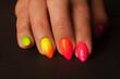 Kolorowe paznokcie przedstawione z bardzo bliska, na ciemnym tle